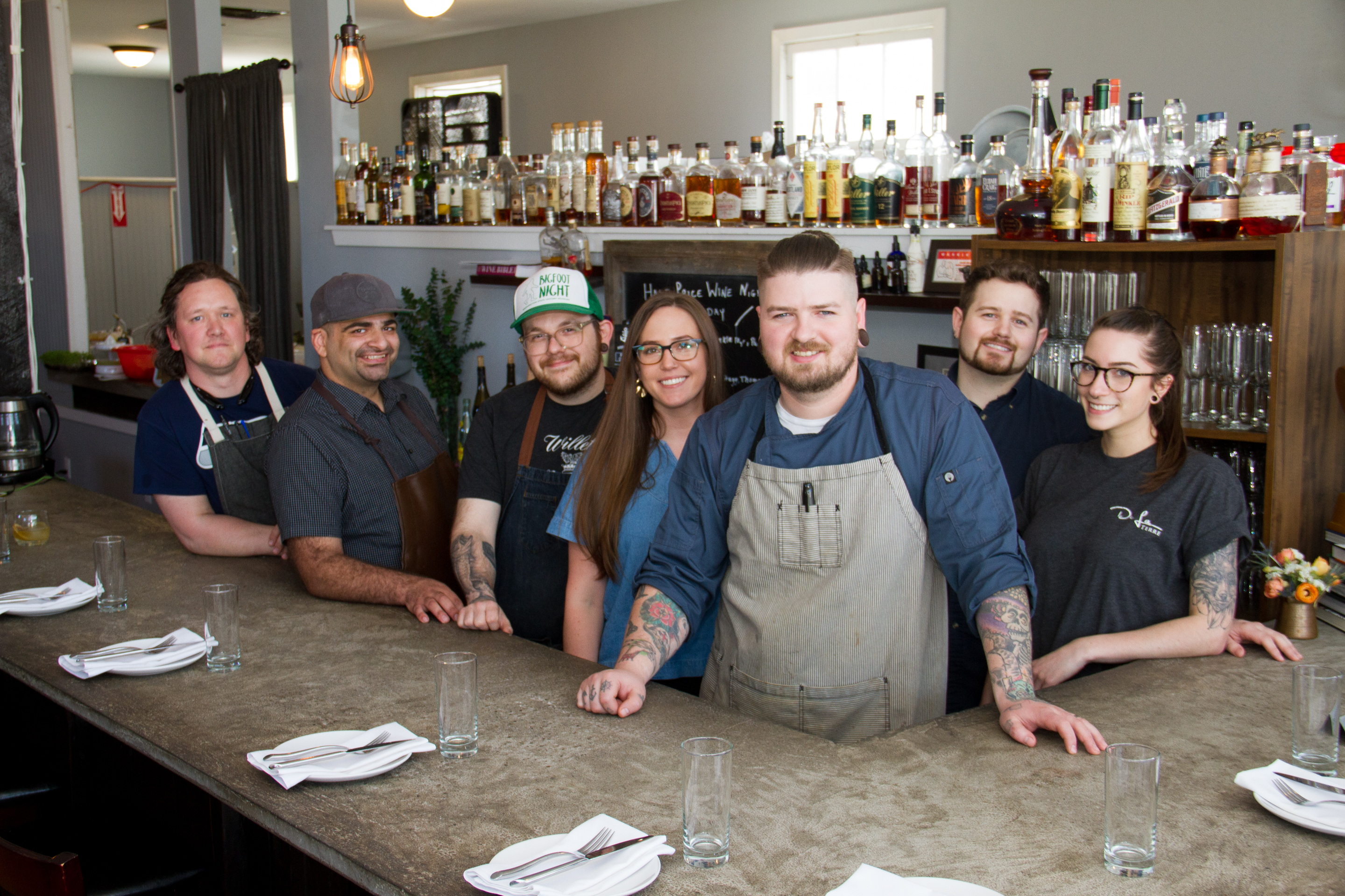 The De La Terre Team poses behind the bar for a group photo.