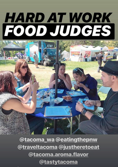 Judges seated at a food-covered table, eating